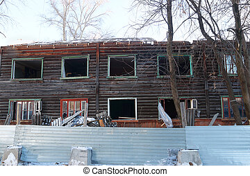 Two-storey abandoned wooden house made of logs on winter day