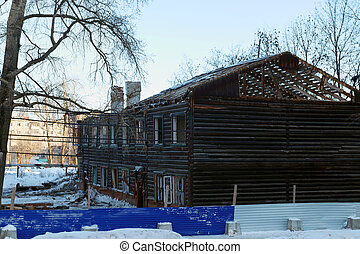 Two-storey abandoned wooden house made of logs on winter...