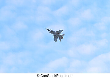 Russian military aircraft MiG-29 flies in blue sky with...