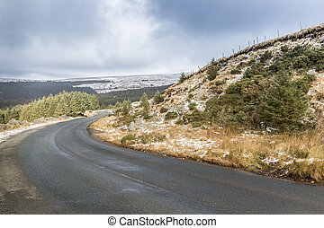 Winding road through Snowy white landscape in Wicklow Gap in...