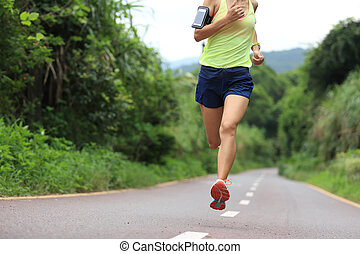 Runner athlete running on forest trail. woman fitness...