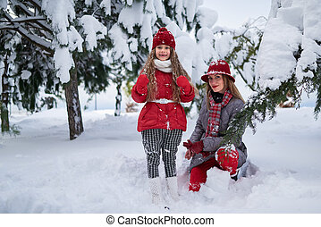 Mother and daughter walking in snowy park - Mother and...
