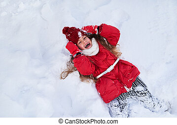 The girl fell into the snow and laughing