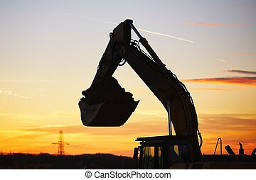 Building site at the sunset - Silhouette of the backhoe in...