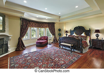Luxury master bedroom with recessed ceiling and fireplace