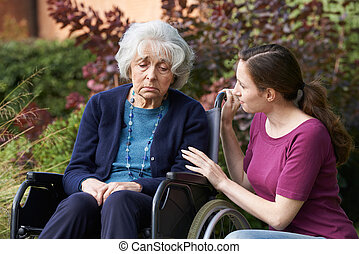 Adult Daughter Comforting Senior Mother In Wheelchair