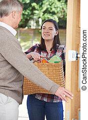 Teenage Girl Doing Shopping For Elderly Neighbour