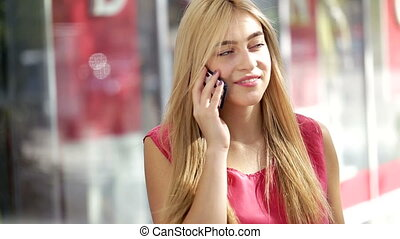Attractive young blonde lady using smart phone in a city mall