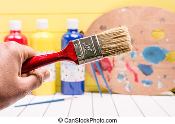 Large paintbrush on a white and yellow background. Palette...
