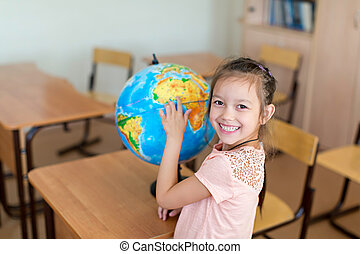 Pupil - Girl with a globe in classroom