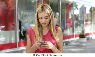 Blonde woman in a rose t-shirt use her mobile phone and smile near the city center