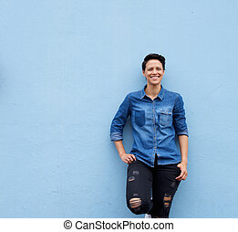 Cool young woman smiling against blue background