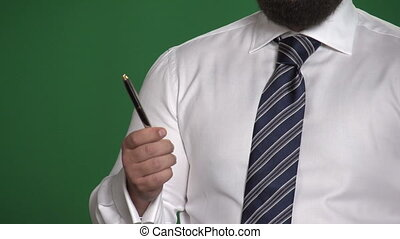 Gesture male hand with a pen on a green background -...