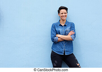Confident young woman smiling against blue background