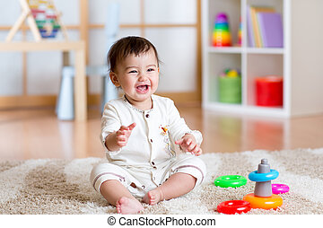 cute cheerful baby playing with colorful toy at home - cute...