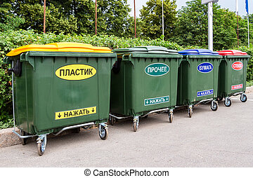 "Green dumpsters on a city street. Text in russian: "" Plastic"", ""Other"", ""Paper"", ""Glass"", ""Press on"""