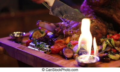 waiter cuts the meat dish in the fire - dish from the chef...