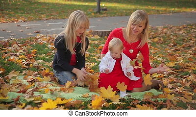 Mom and Two Daughters in Autumn Park