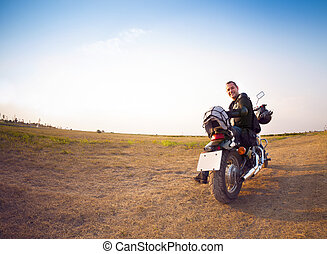 Biker on the country road against the sky - Portrait of a...