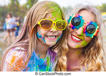 Happy mother with little daughter on holi color festival -...