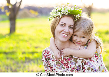 Happy mother and her little daughter in a blossoming garden