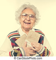 elderly woman holding old envelops