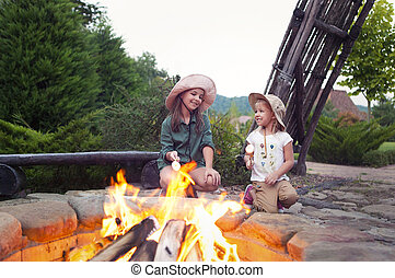 Two happy sisters roasting marshmallows
