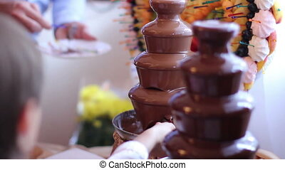 people eating fruits with chocolate - chocolate fountain...