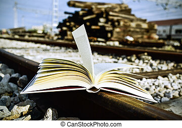book on the railroad tracks - closeup of an open book on the...