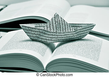 paper boat on an open book, black and white - closeup of a...