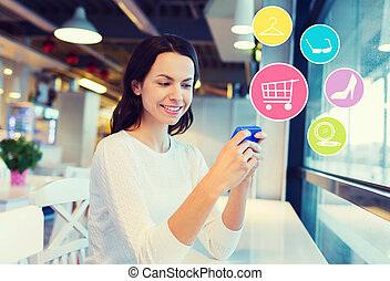 smiling woman with smartphone shopping online - people,...