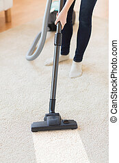 close up of woman legs with vacuum cleaner at home - people,...