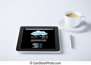 tablet pc with weather forecast and cup of coffee -...