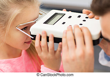 optician with pupillometer and girl at eye clinic - health...