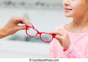 close up of girl taking glasses at optics store - health...