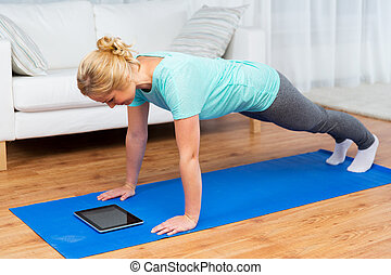 woman with tablet pc doing plank exercise at home - fitness,...