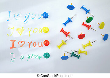 Love you letter with colorful push pins. Sunlight shadows...