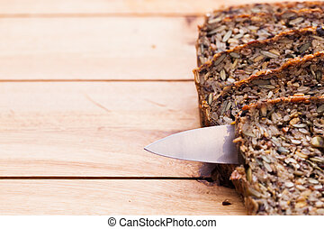 Knife in wholemeal, wholewheat bread on wooden table....