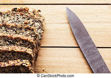 Knife and wholemeal, wholewheat bread on wooden table....
