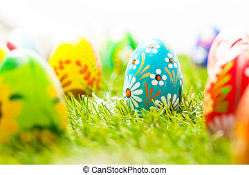 Colorful hand painted Easter eggs in grass Spring theme,...