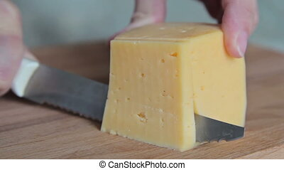Woman cutting piece of cheese