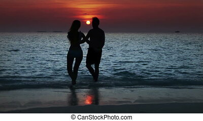 Silhouette of the man and woman, going to the sea on a sunset and kissing in waves