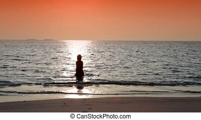 Silhouette of the woman against a sunset at ocean