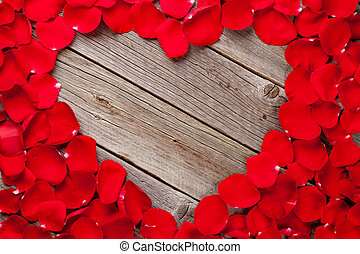 Red rose petals heart over wooden table Top view with copy...