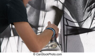 Male artist drawing black and white graffiti - Close-up shot...