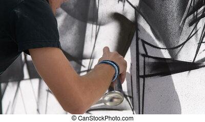 Male artist drawing black and white graffiti - Close-up shot...