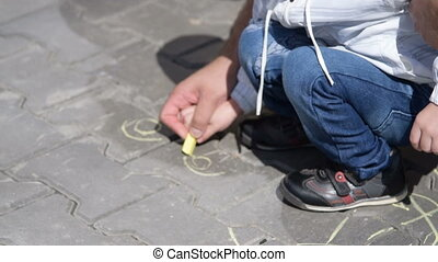 Father and son drawing on sidewalk