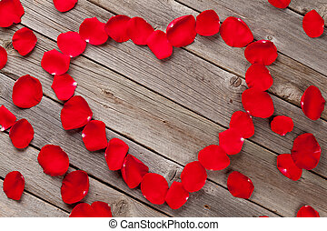 Red rose petals heart over wooden background with copy space