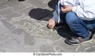 Little boy drawing with chalk on asphalt - Little child...