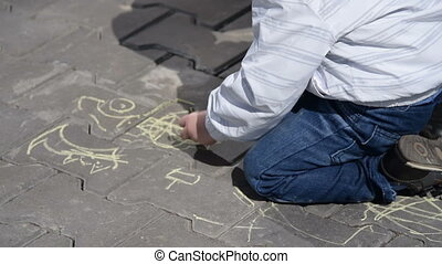 Little child drawing with chalk outdoor - Little boy making...